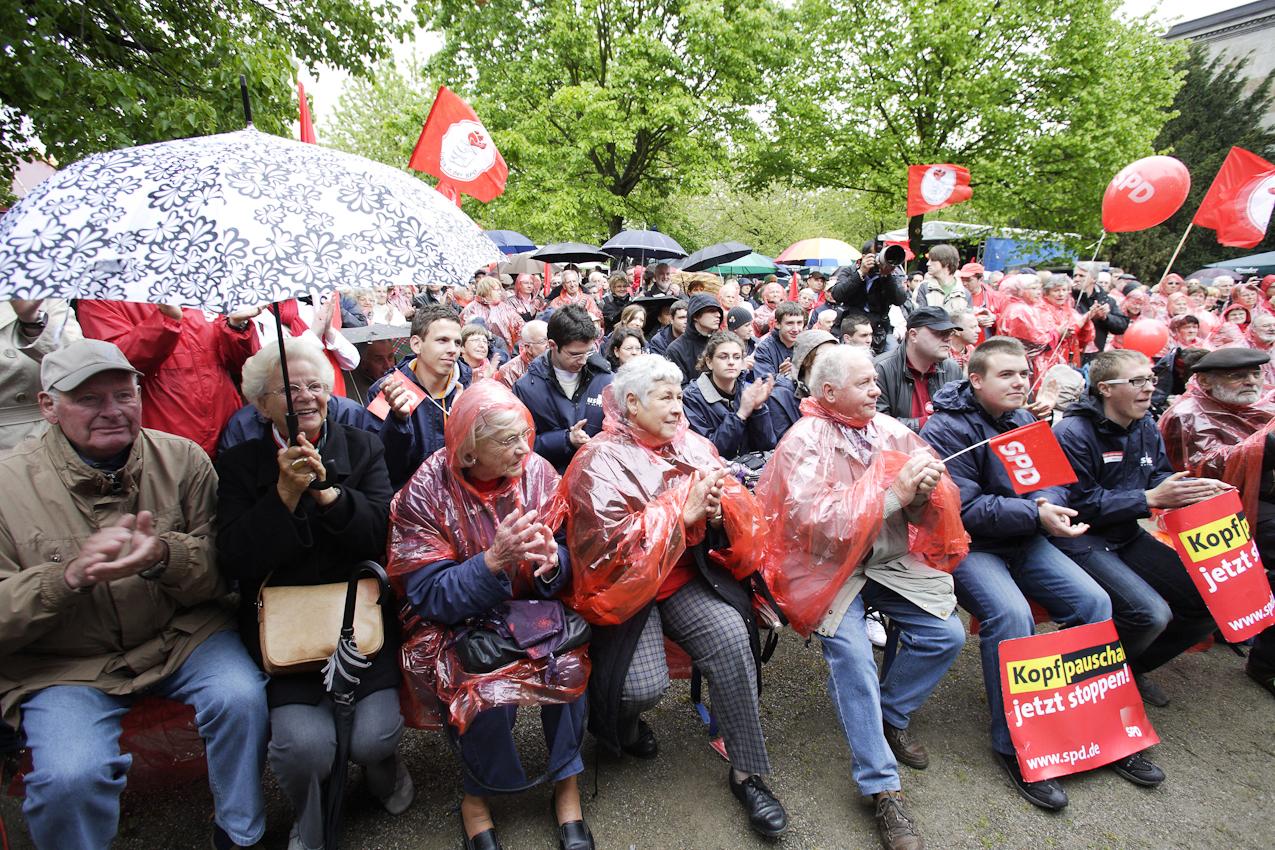 Mit  Regenkaps und Schirmen geschützt, applaudieren die Teilnehmer der Kundgebung beim Familienfest der NRW-SPD den Rednern.