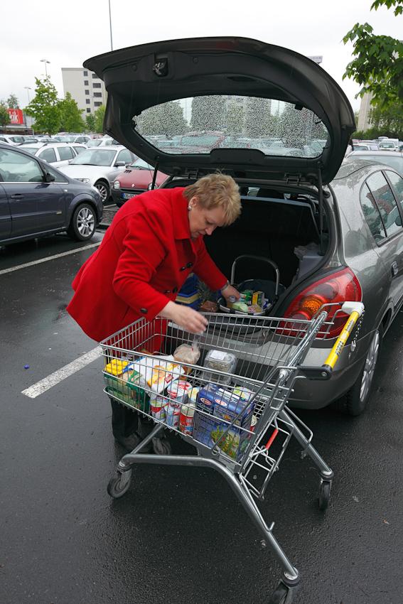 Die gekauften Waren werden in den Kofferraum eines Pkw verladen.