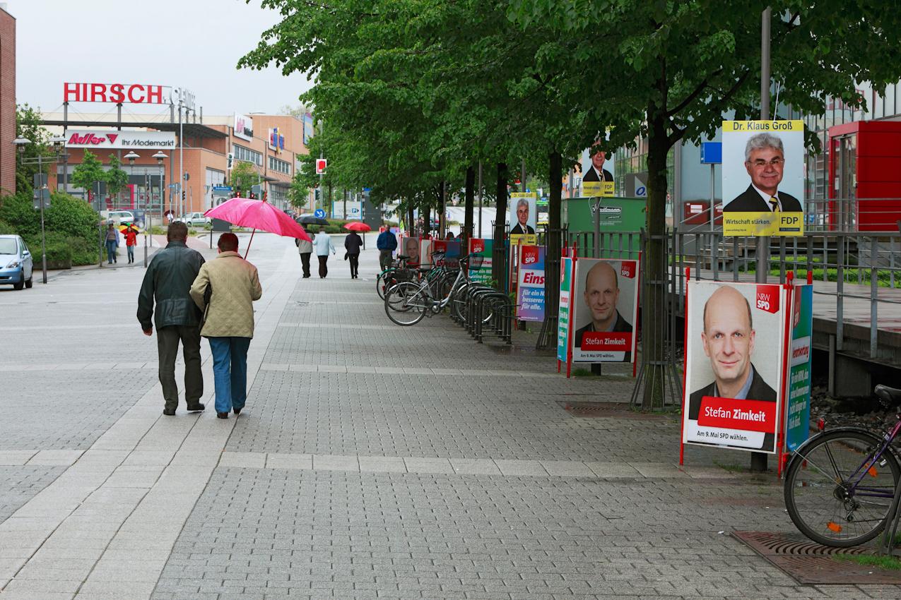 Landtagswahl 2010 in Nordrhein-Westfalen, Fußgängerzone in Oberhausen-Sterkrade: zwei Tage vor der Wahl spazieren Menschen mit Regenschirmen gelangweilt an Wahlplakaten vorbei.