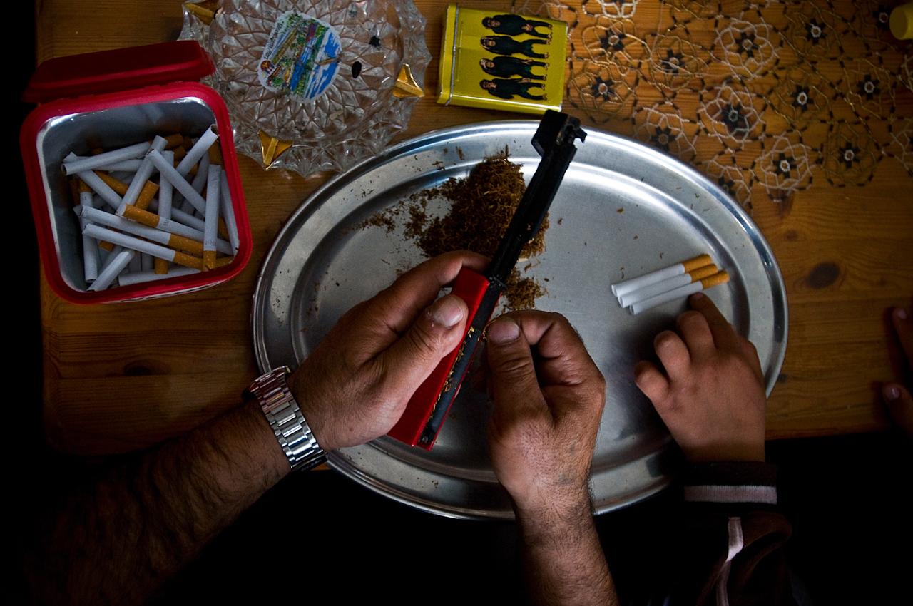 Arif Gasjoni dreht Zigaretten, während sein kleiner, 8. Sohn mit den Hülsen spielt.